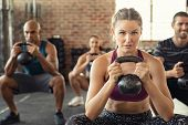 Group of fit people holding kettle bell during squatting exercise at gym. Fitness girl and men lifti poster