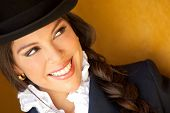 Portrait of a beautiful horsewoman wearing a hat and smiling