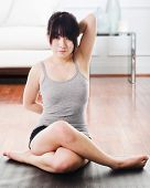 Asian woman sitting on a yoga mat doing the cow face pose.