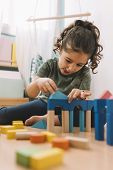 Little Girl Playing Concentrated In The Floor With Colorful Wooden Building Block Toys At Home Or Ki poster