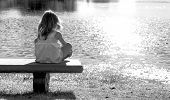 a young lonely girl sitting on a bench