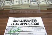 stock photo of self-employment  - Approved small business loan application and dollar bills - JPG