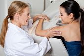 stock photo of mammogram  - Mature female doctor assisting young patient during mammography - JPG