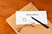 Divorce decree and envelope on wooden background