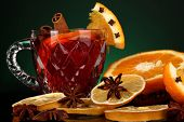 Fragrant mulled wine in glass with spices and oranges around on green background