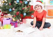 Little boy in Santa hat with milk, cookies and letter for Santa Claus