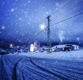 Photo of blizzard in the village, snow falling on the house, night wintertime landscape, Christmasti