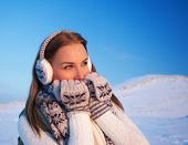 Picture of pretty woman enjoying winter vacation, active lifestyle, beautiful girl having fun in mountains covered snow, stylish female wearing knitted gloves and warm earmuff, wintertime holidays