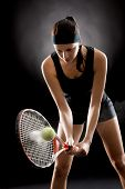 Female tennis player with racket and ball on black background