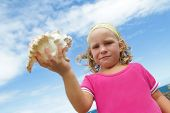 cute smiling child girl with big sea shell