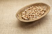 chickpea (garbanzo) beans in a rustic wood bowl against burlap canvas