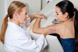 picture of mammography  - Mature female doctor assisting young patient during mammography - JPG