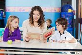 picture of daycare  - Beautiful teacher reading book while children listening to her in classroom - JPG