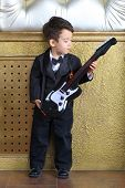 A little boy in black tuxedo stands near a wall with a guitar