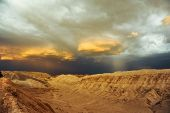 Thunderstorm developing over sand dune in Valle De La Luna in the Atacama Desert near San Pedro de Atacama, Chile. The Atacama Desert is one of the driest places on earth, and these storms are rare.