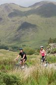 Athletic couple biking through wilderness with imposing mountain in background