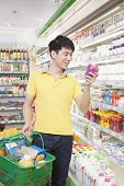 Smiling Young Man Looking At Food in Supermarket