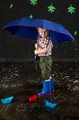 Smiling little boy sheltering from water beneath blue umbrella