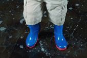 Childrens legs wearing blue rubber boots and shorts in the water