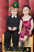 Smiling little boy and girl sitting on an old radiogramophone on the red background wall