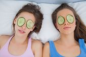 Friends lying in bed with cucumber slices on eyes at sleepover