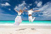 Wedding Couple Jumping On The Beach