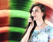 A beautiful teen soloist happily singing into her microphone with plenty of space for your text on h