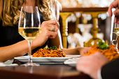 stock photo of spaghetti  - happy couple have a romantic date in a fine dining restaurant - JPG