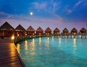 foto of roof-light  - houses on piles on water at night in fool moon light - JPG