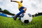 stock photo of game-fish  - Boy soccer player hits the ball on the football field - JPG