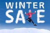 Woman Jumping Among The Word Winter Sale