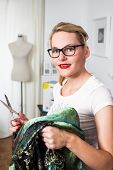 stock photo of thread-making  - Young caucasian fashion designer with scissors in hand and mannequin in the back - JPG
