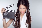 Beautiful Brunette Woman Holding Clapper Board Against A Grey Background