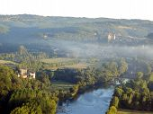 stock photo of chateau  - Dordogne landscape at sunrise, as seen from a hot air balloon. Chateau des Milandes can be seen on the left with the River Dordogne flowing to Chateau de Beynac in the background