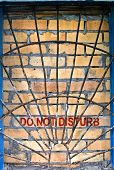Do Not Disturb Label On The Brick-encased Window With Railings