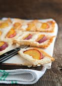 stock photo of phyllo dough  - Phyllo Tart With Sugared Peaches on wooden coking board - JPG