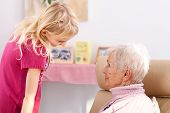 stock photo of polite girl  - Little girl in rose sweter talking with grandmother - JPG