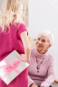 picture of polite girl  - Young girl giving some present for grandma - JPG