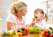 pic of child feeding  - mother feeding kid daughter vegetables in kitchen - JPG
