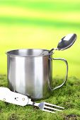 Metal mug, spoon and fork on green grass, on nature background