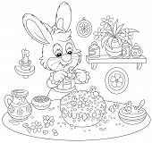 stock photo of fancy cakes  - Easter rabbit decorating a fancy cake for the holiday table - JPG