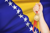 Medal In Hand With Flag On Background - Bosnia And Herzegovina