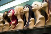 stock photo of wig  - a row of mannequins on a shelf in a wig shop - JPG
