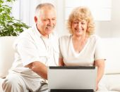 picture of elderly couple  - Happy smiling elderly couple working with laptop at home - JPG