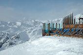 Deckchairs standing on peak In Alps In Winter