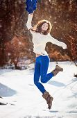 Attractive brunette girl with white sweater posing playing in winter scenery. Beautiful young woman