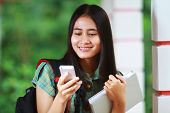 Smiling Asian Student Holding Book And Reading Text Message
