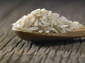 Raw brown rice in spoon on wooden background