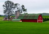 image of red barn  - Red barn with a green roof surrounded by green fields - JPG