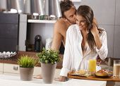 Loving couple kissing in the kitchen in the morning.